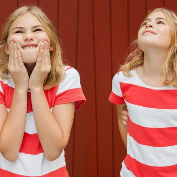Lifestyle photo of adolescent girl in red and white shirt making funny faces.