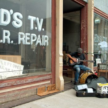 Blues musician in doorway of abandoned store, Helena, Arkansas