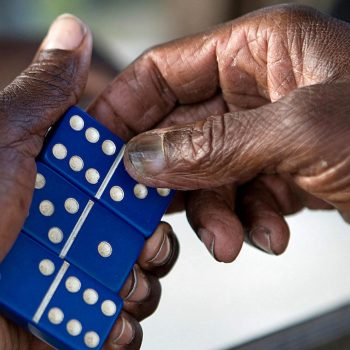 Close up of old black hands with dominoes. The Bahamas