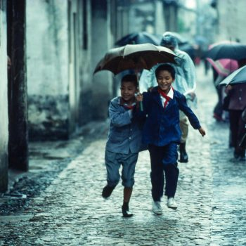 Young boys running with umbrella in rain, Suzchou, China