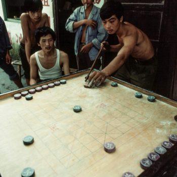 Young men playing game in Chinese hutong, Guangzchou (Canton), China