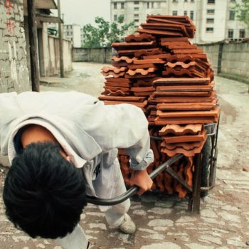 Man pulling heavy load of red tiles, Suzchou, China