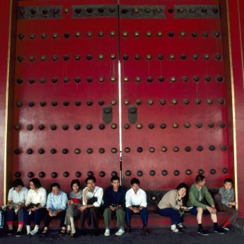People sitting in front of large doors at the Forbidden City, Beijing, China