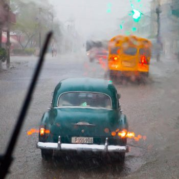 Classic automobile in torrential downpour in Havana, Cuba