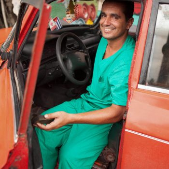 Portrait of man in green scrubs in orange car, Havana, Cuba
