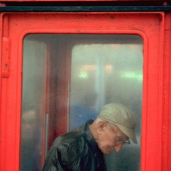 Man in British telephone booth, Blackpool, England, UK