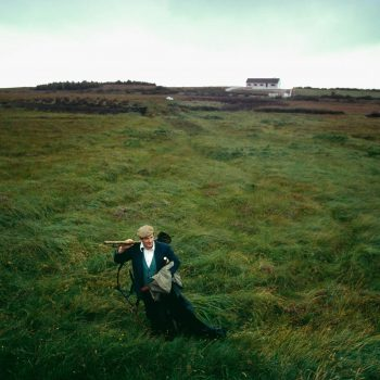 Man walking across peat field, Ireland