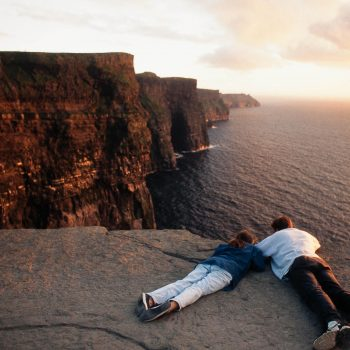 Couple looking over edge at Cliffs of Moher, Ireland