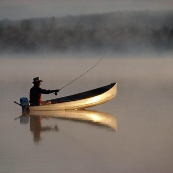 Fly fishing from canoe early morning calm lake with reflections Adirondacks, NY