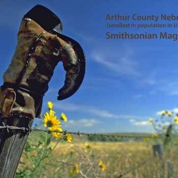 Old cowboy boot on fence pointing to cemetery, Arthur County, Nebraska