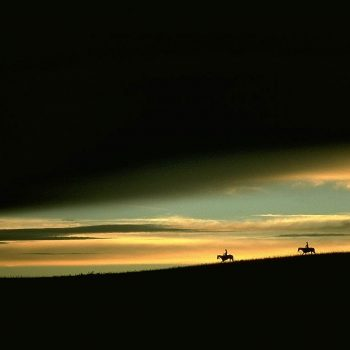 Horse riders silhouetted against dramatic sunset sky, Nebraska sand hills.