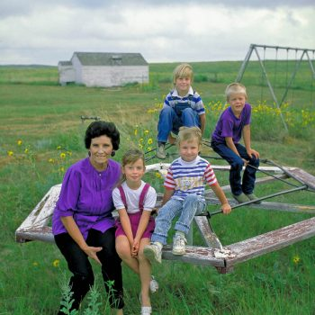 Teacher and children on overgrown playground, Arthur County, Nebraska