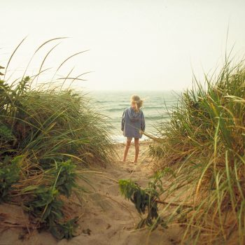 Young girl in sand dunes looking at ocean, Block Island, Rhode Island