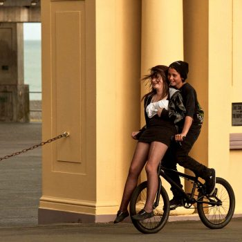 Young couple having fun on bicycle, New Zealand