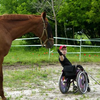 Young man in wheelchair working with horse at Viola Majewska's hippotherapy stable. Opening Our Eyes Movie.