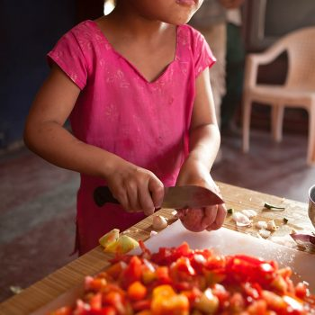 Child cutting vegetables at the Kopila Childrens Home, Surkhet, Nepal. Opening Our Eyes Movie.