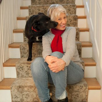 Mature woman at home on stairway with black dog