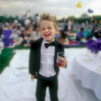Young boy in tuxedo at concert picnic, Central Park, NYC