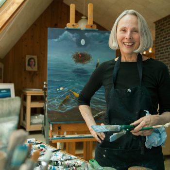 Mature woman artist in studio with paintings
