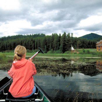 Young girl in canoe paddling, Seeley Lake, Montana