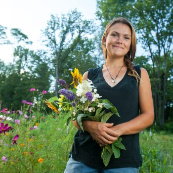 Portrait of young female organic farmer with flowers in field